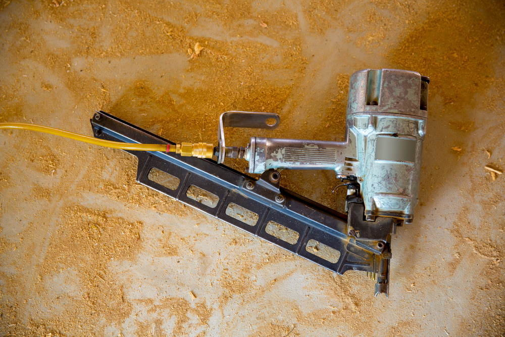 old nail gun surrounded by sawdust