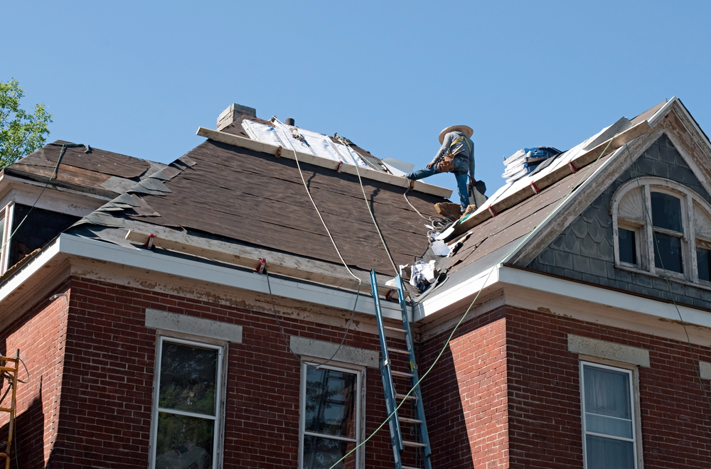 man replacing shingles on old brick home